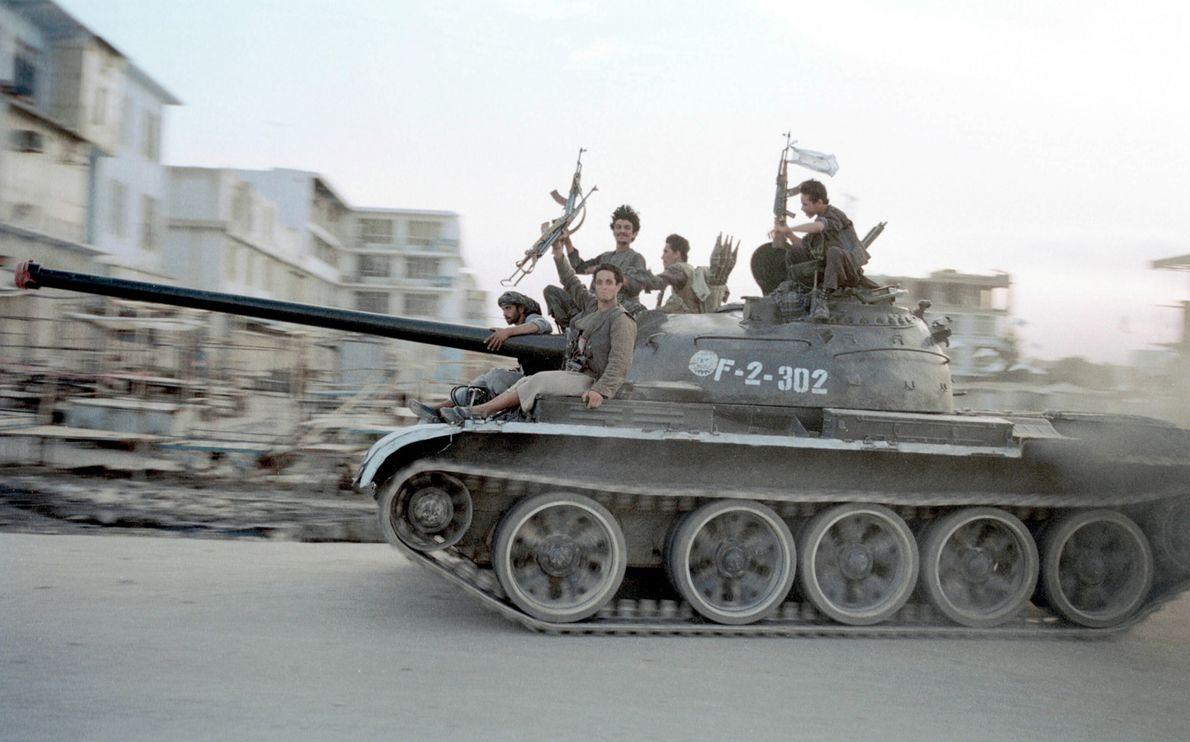 Soldados talibanes conducen un tanque soviético