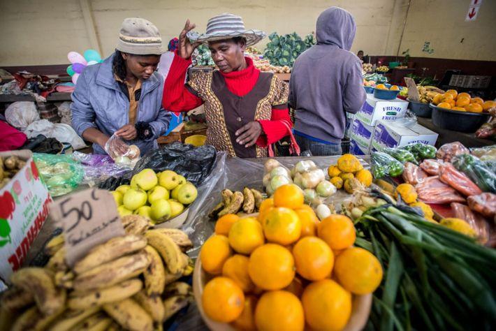 Unas mujeres compran productos en un mercado de Manzini