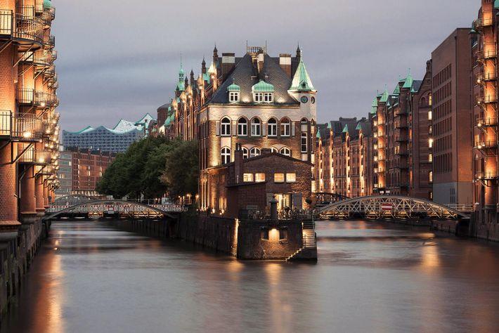 El Castillo del Agua brilla en la noche del distrito de los Almacenes de Hamburgo.
