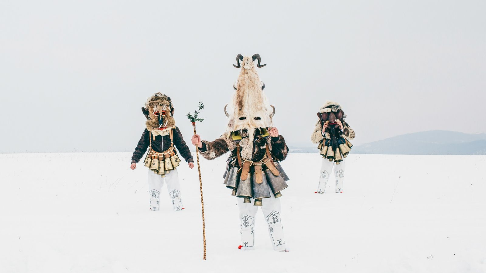 Tres kukeri de pie sobre la nieve