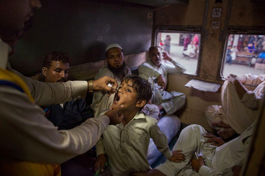 Un trabajador sanitario que busca a personas si vacunar en Karachi, Pakistán, encuentra a un niño ...