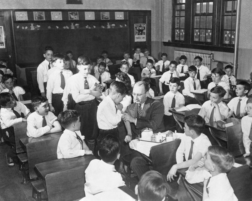 Los niños de la Escuela Católica Santa Juana de Arco de Queens, Nueva York, hacen cola ...