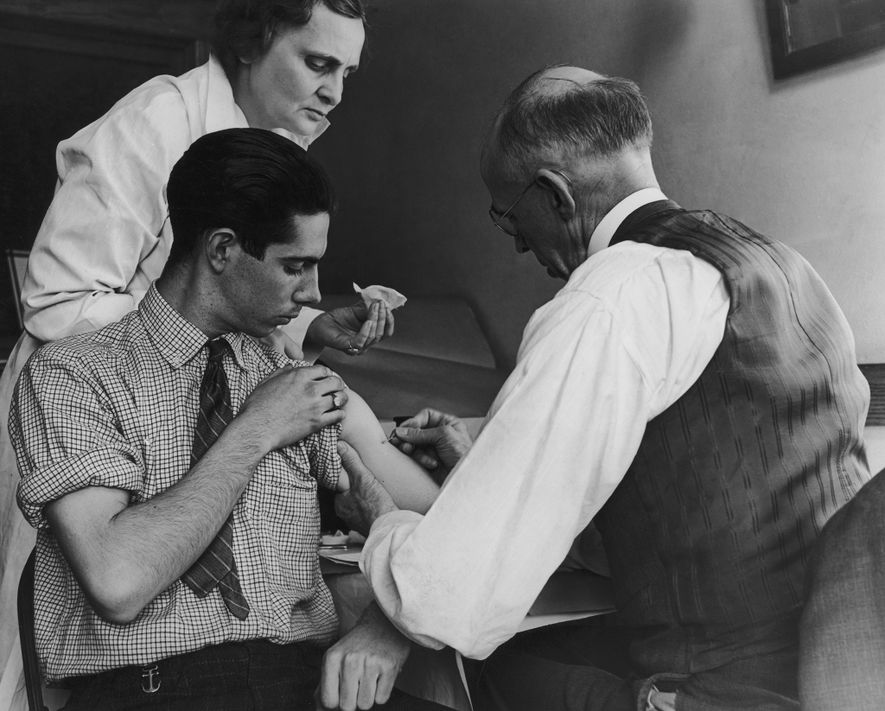 Un médico escolar y una enfermera del condado vacunan a un joven contra la viruela en ...