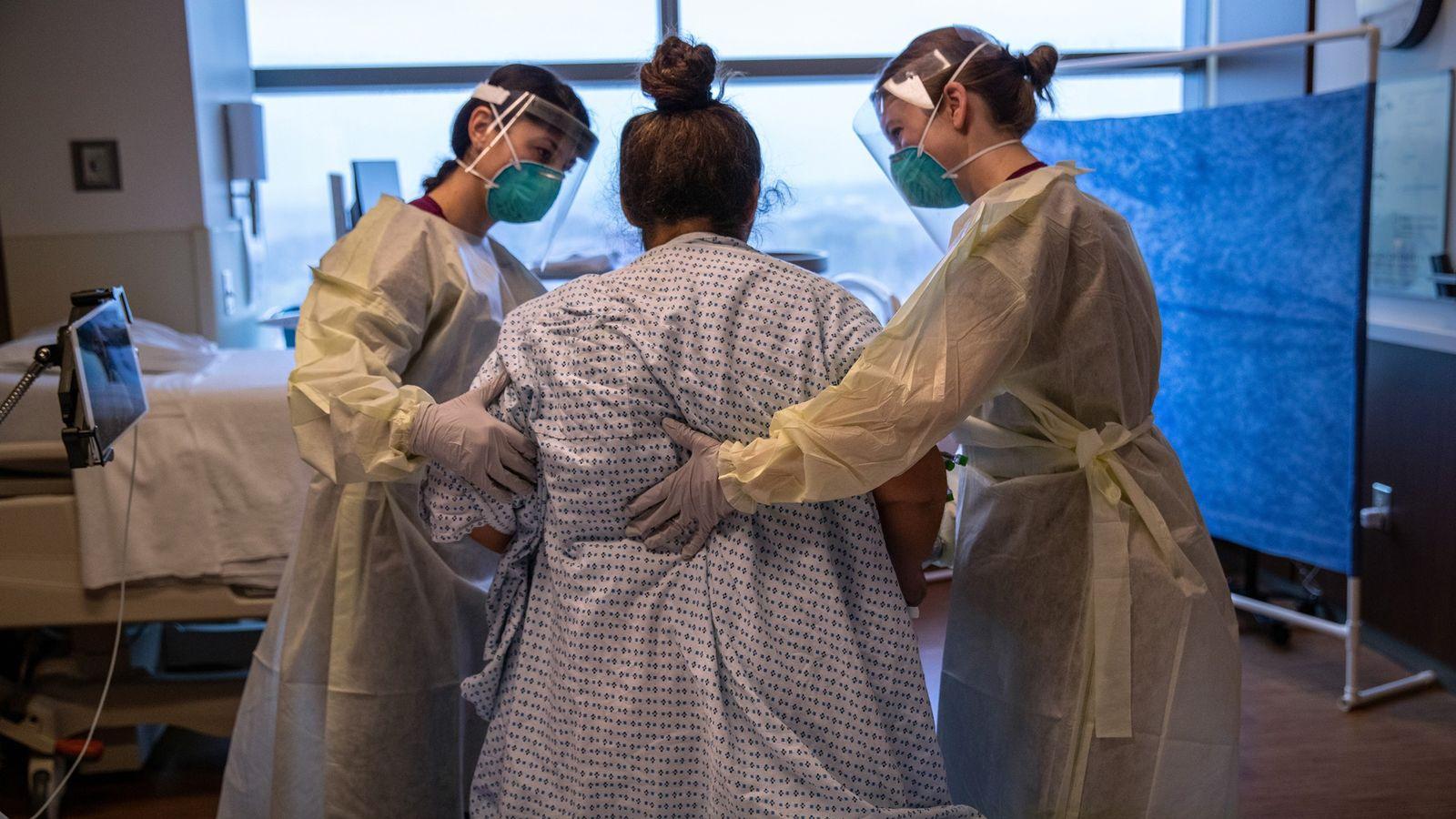 Trabajadoras ayudan a una paciente