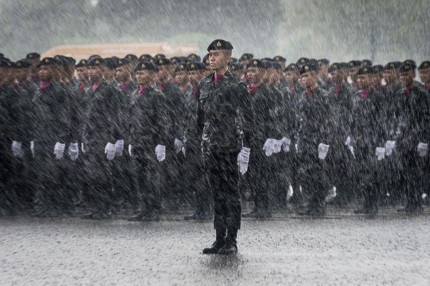 Los cadetes del ejército tailandés permanecen firmes mientras llueve intensamente.