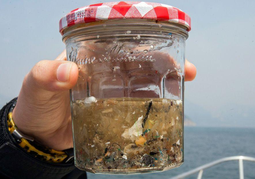 Un estudiante de ciencias medioambientales de la Universidad de Hong Kong sostiene un tarro que contiene ...