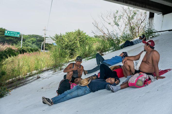 Los centroamericanos que viajan en la primera caravana de migrantes descansan bajo un paso elevado de ...