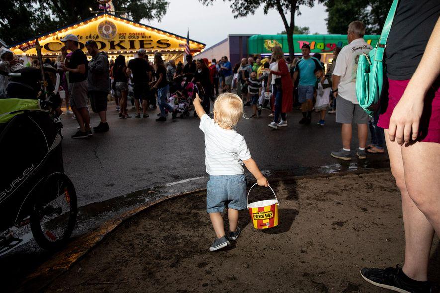 Un niño se dirige hacia Sweet Martha's, un puesto básico de la Feria Estatal de Minnesota, que vende galletas en cubos.