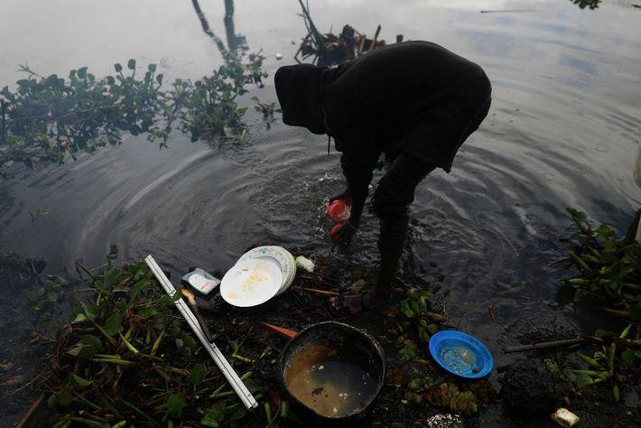 Un pescador lava los platos en el lago Naivasha