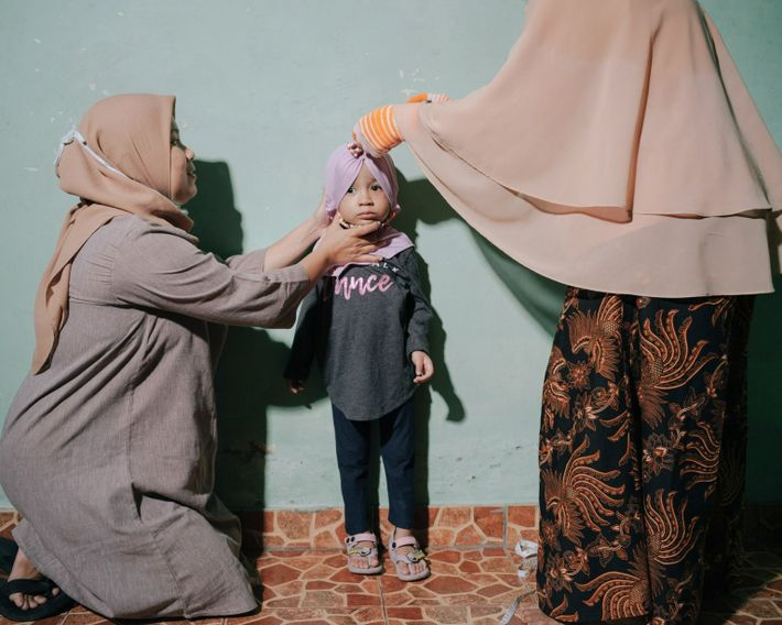 Madre sostiene a su hija mientras la miden