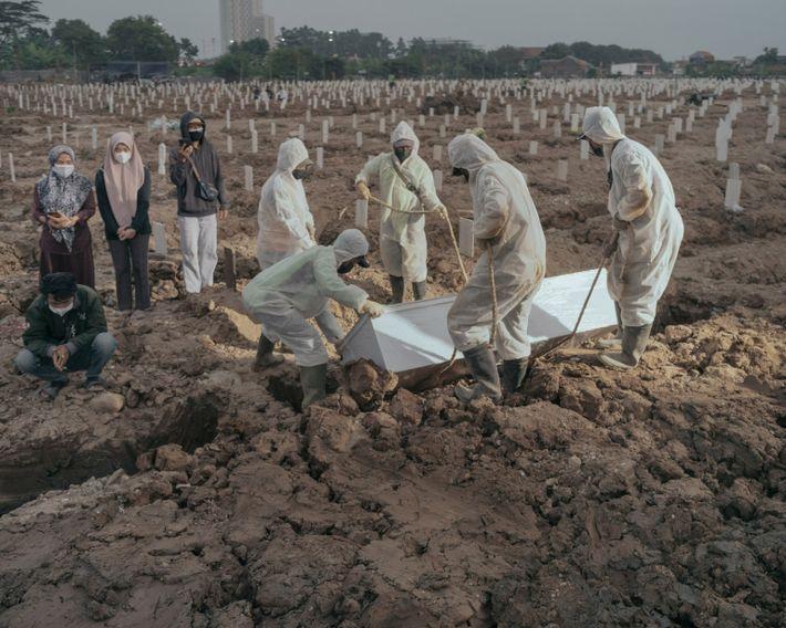 Los trabajadores entierran a una víctima de la COVID