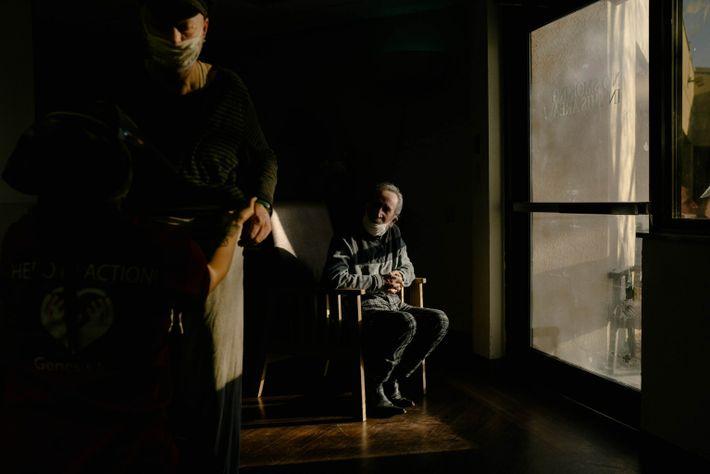 Salvador Arvizu sentado junto a una puerta de cristal