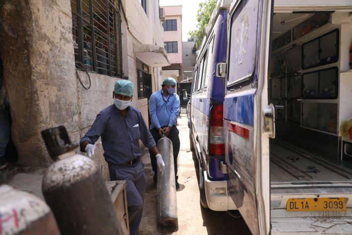 Ajay Kumar y Gaurav Kumar llevan oxígeno a una ambulancia