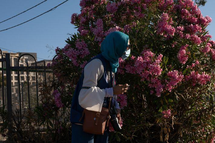Una mujer se refugia tras un arbusto