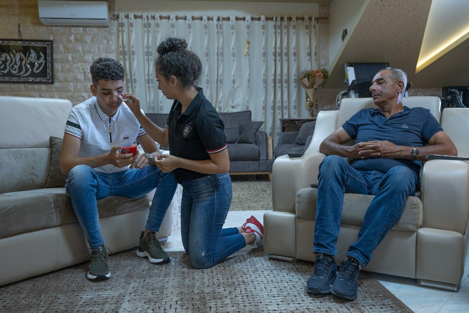 Basil Abu el-U'la, de 15 años, con su padre y su hermana mayor
