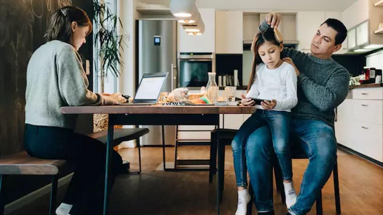 Imagen de una madre trabajando mientras el padre peina a su hija