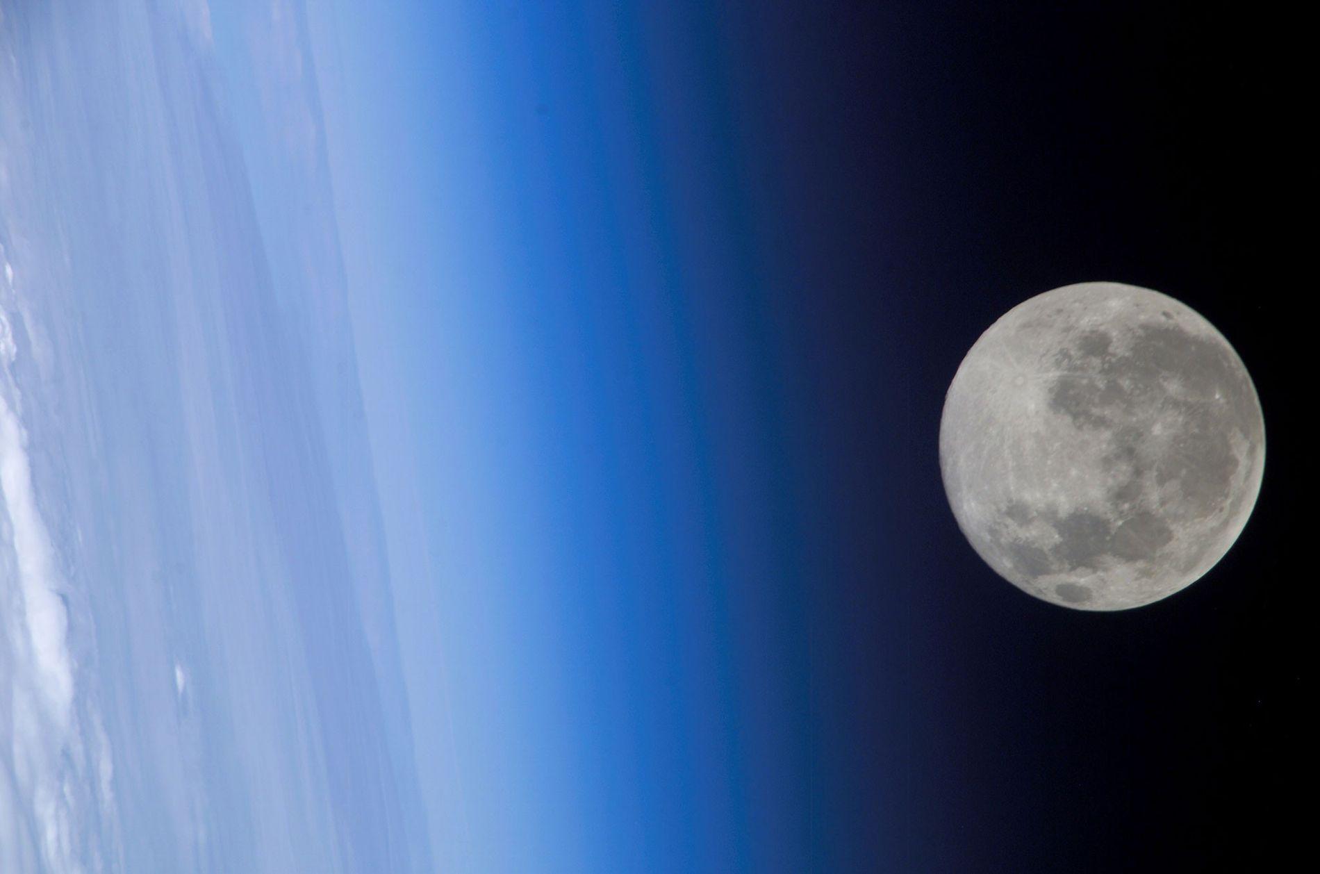 Una luna llena, vista desde la Estación Espacial Internacional, parece rozar la atmósfera terrestre.