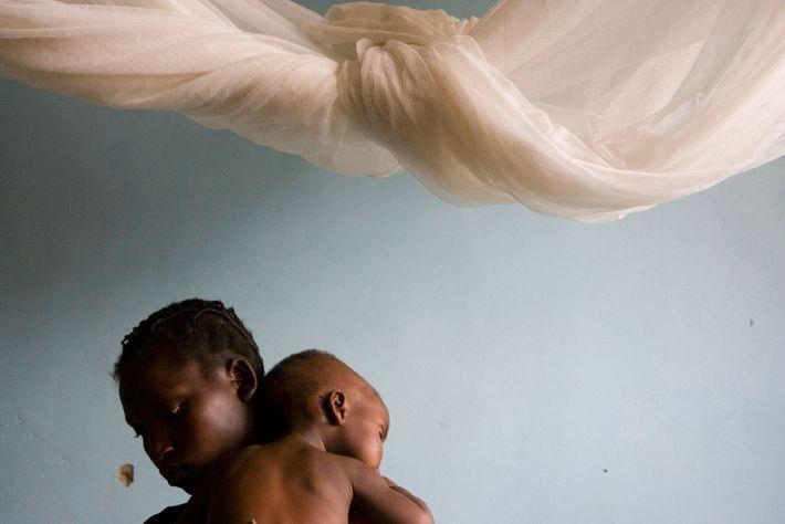 Fotografía de una madre que consuela a su hijo enfermo de malaria