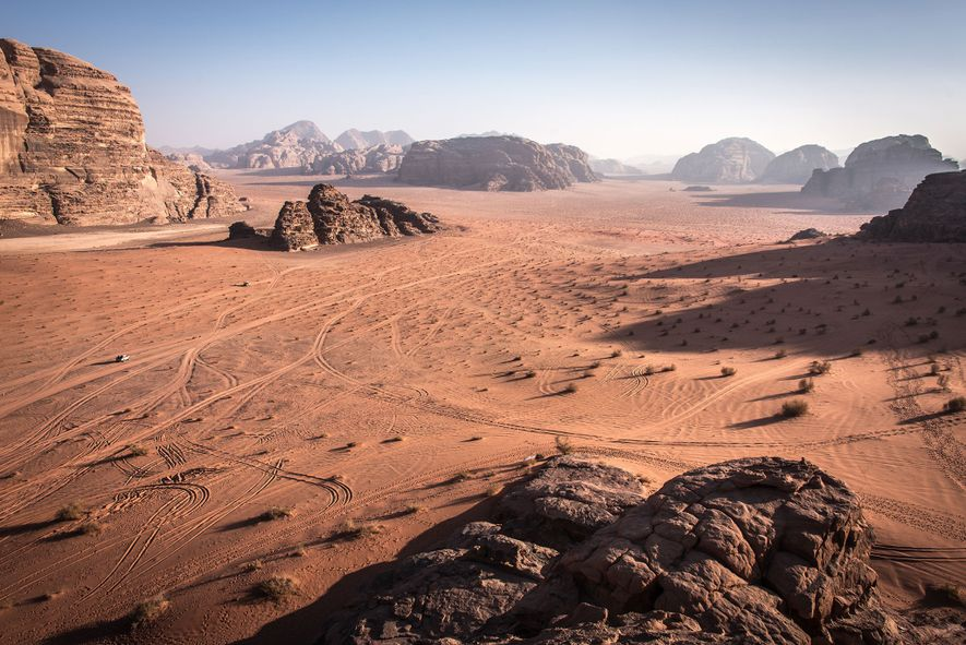 Fúndete con el vasto paisaje desértico de Uadi Rum, alterado solo por los pilares de arenisca ...