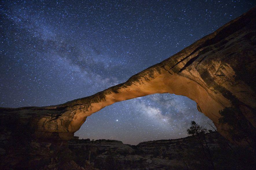 Una noche estrellada sobre el puente de Owachomo en el monumento nacional de los Puentes Naturales, ...