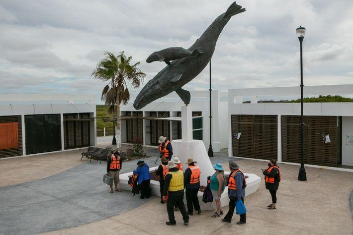Turistas junto a la escultura de una ballena gris y su cría