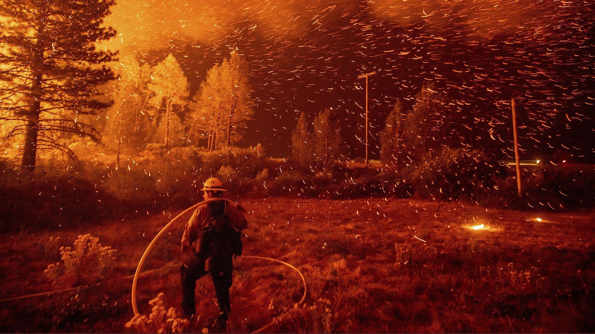 Las ascuas vuelan sobre un bombero que trabaja para contener el incendio de Delta, en el bosque nacional Shasta-Trinity, en California, en 2018. El tamaño de las llamas se triplicó de la noche a la mañana.