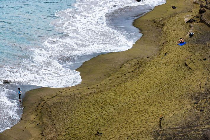 Imagen de visitantes sobre la arena verde de Papakolea Beach en Hawai