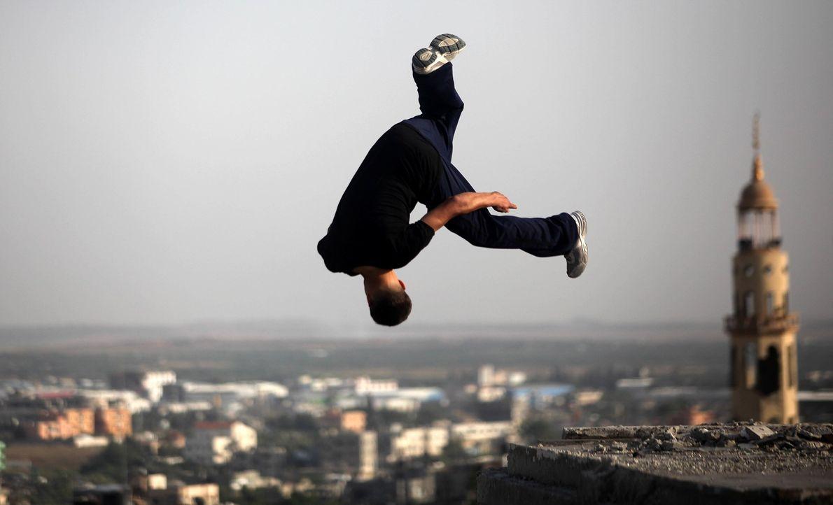 Un adolescente pone en práctica sus habilidades de parkour sobre las ruinas de edificios destruidos de …