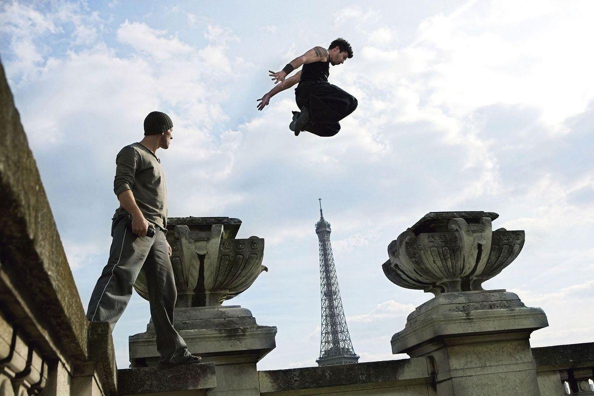Un atleta de parkour se desplaza sobre un muro frente a la torre Eiffel en París, …