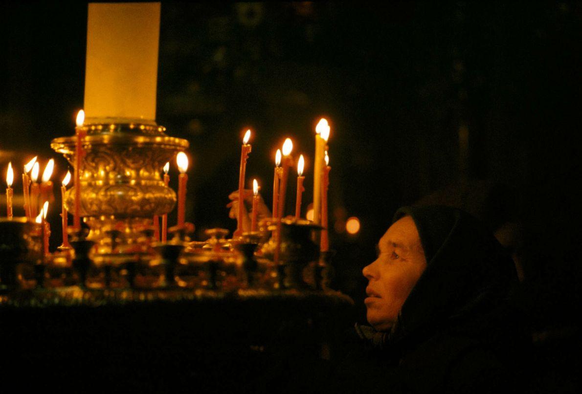 Una mujer enciende una vela en una iglesia rusa ortodoxa