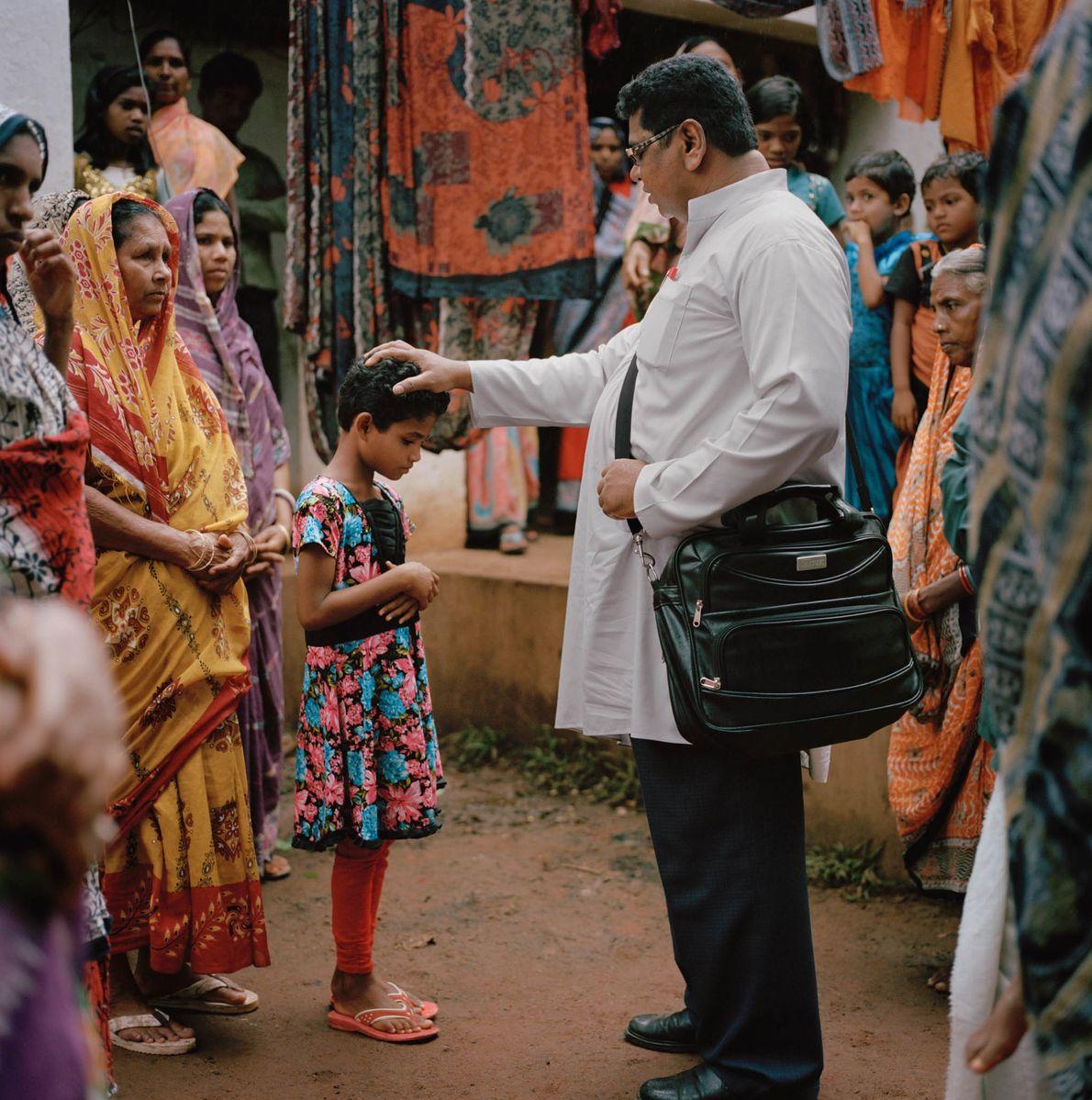 Sacerdote bendice a una niña