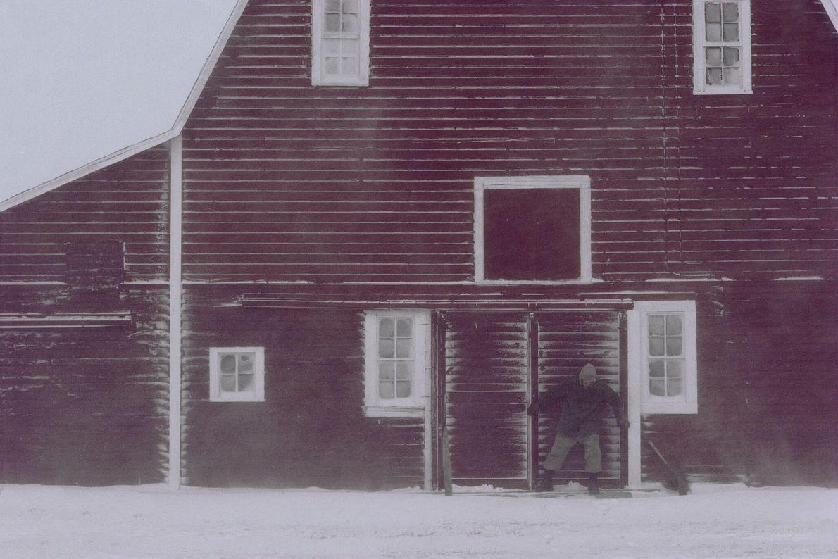 Un ganadero cierra la puerta del establo