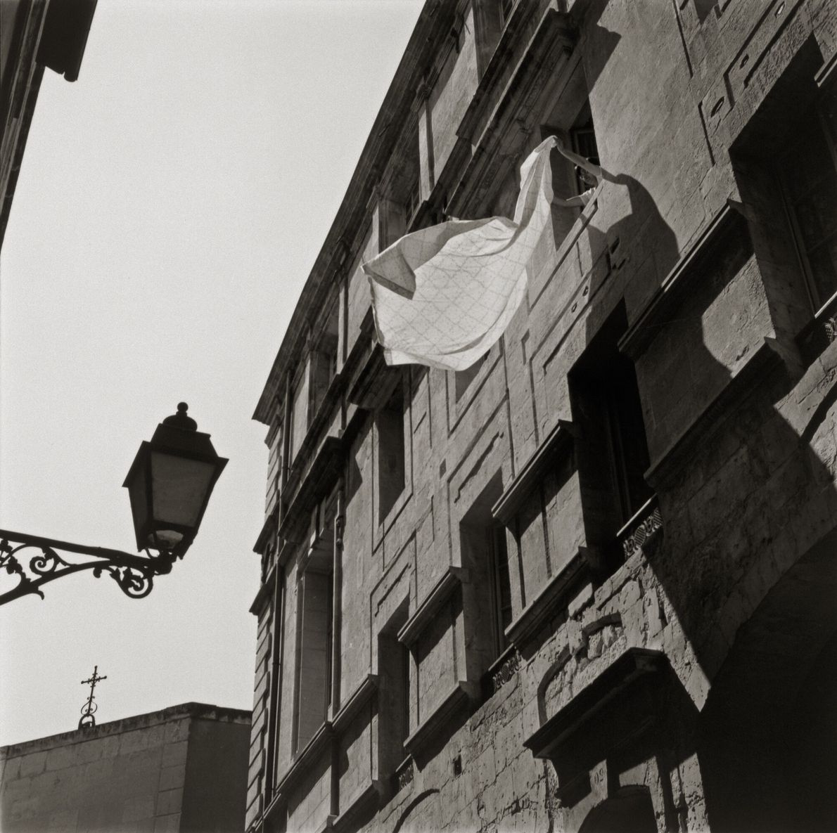 Imagen de una persona sacudiendo una sábana por la ventana en Arles, Francia