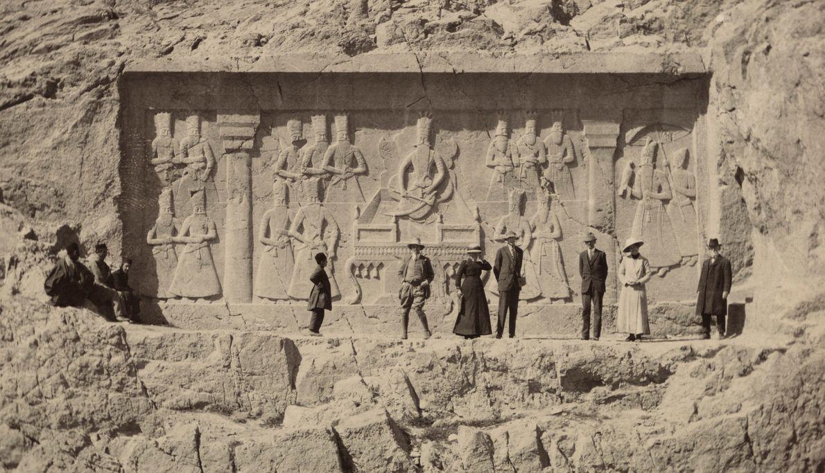 Imagen de turistas frente a una talladel siglo XIX al sur de Teherán, Irán