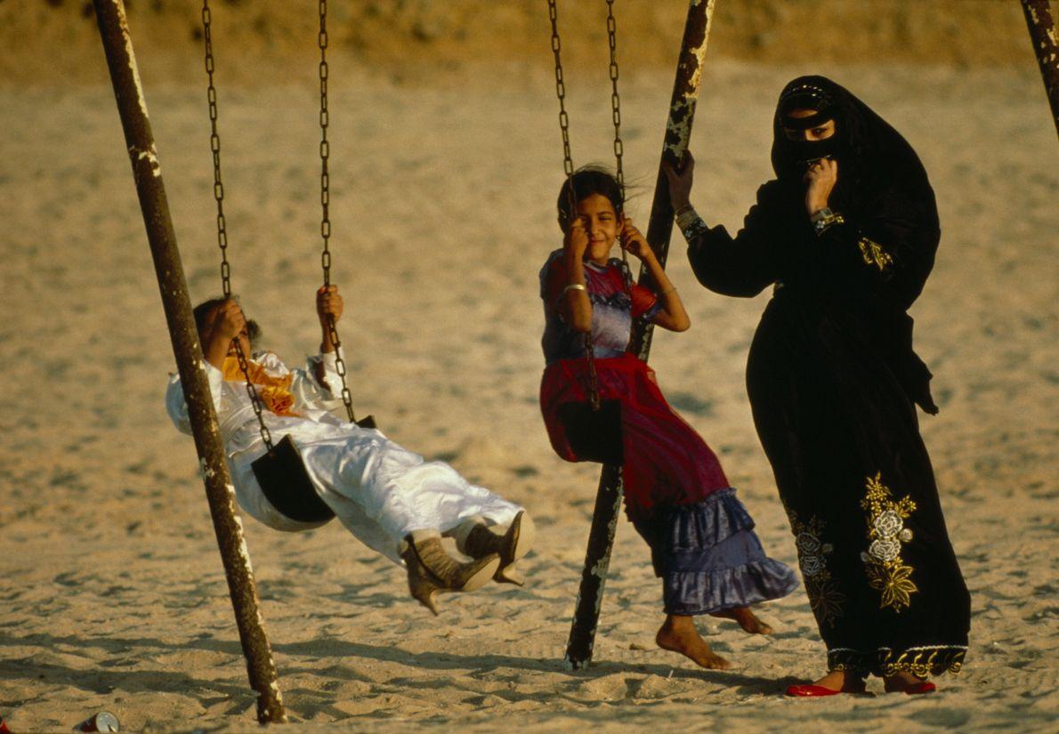 Imagen de una mujer de Arabia Saudí que lleva un velo mientras vigila a dos niñas ...