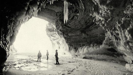Tres personas en la entrada de una cueva con nieve alrededor y carámbanos de hielo en ...