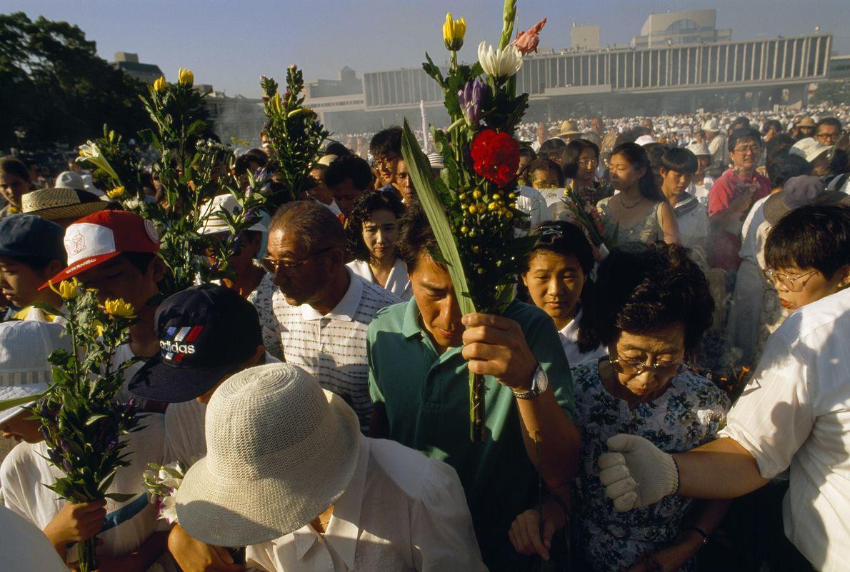 Imagen de la gente llevando flores durante el evento conmemorativo en Hiroshima, Japón