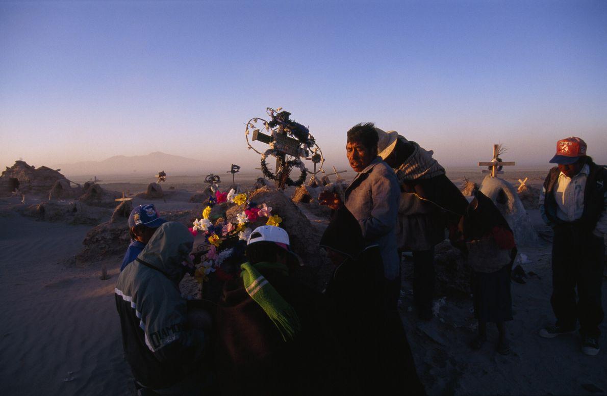 Imagen de una familia chipaya en Bolivia rezando en un cementerio.