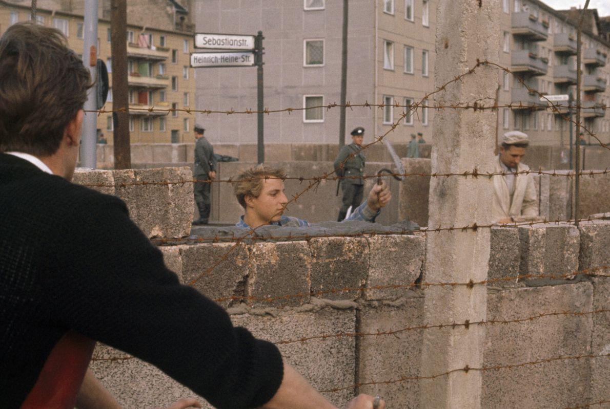 Imagen de albañiles alemanes poniendo cemento en el Muro de Berlín en 1961