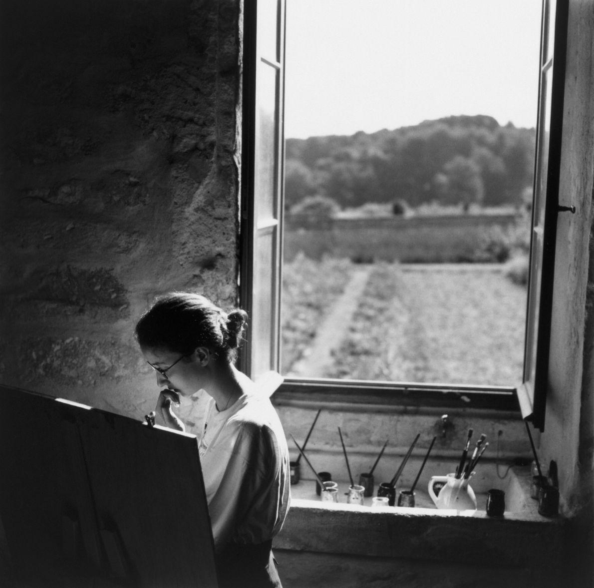 Imagen de una mujer pintando junto a una ventana abierta en un hospital psiquiátrico de Francia