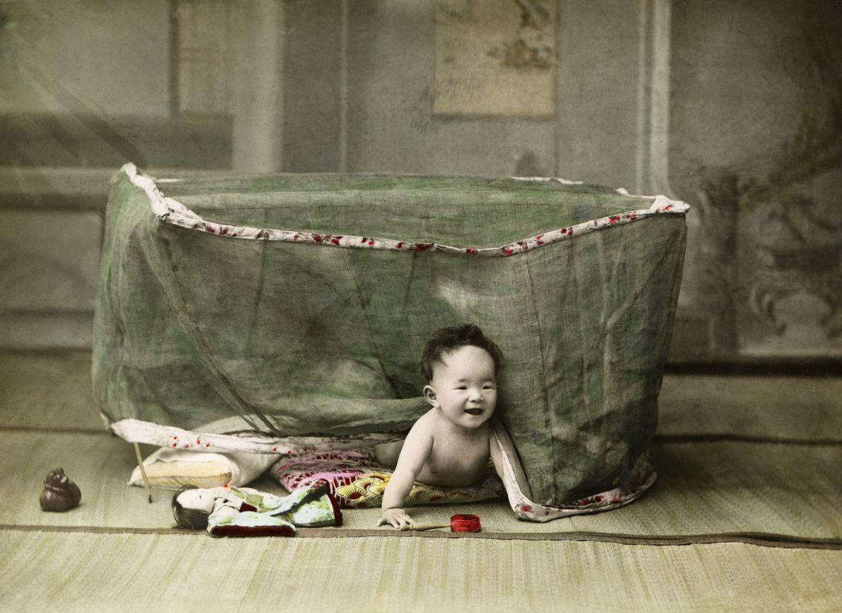 Imagen de un bebé japonés gateando por debajo de una red de su corralito de juego
