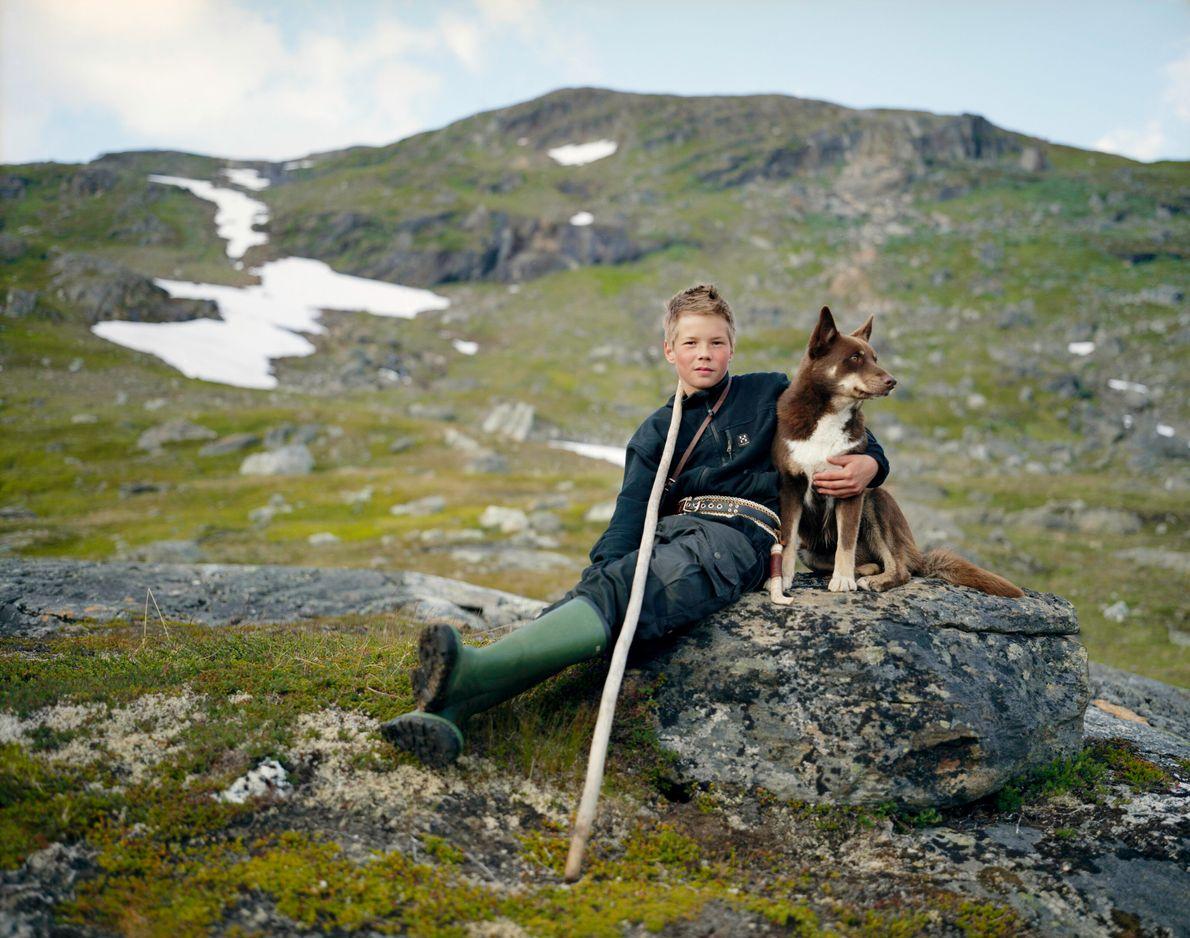 Imagen de un niño lapón y su perro marrón y blanco sentados en una piedra en ...