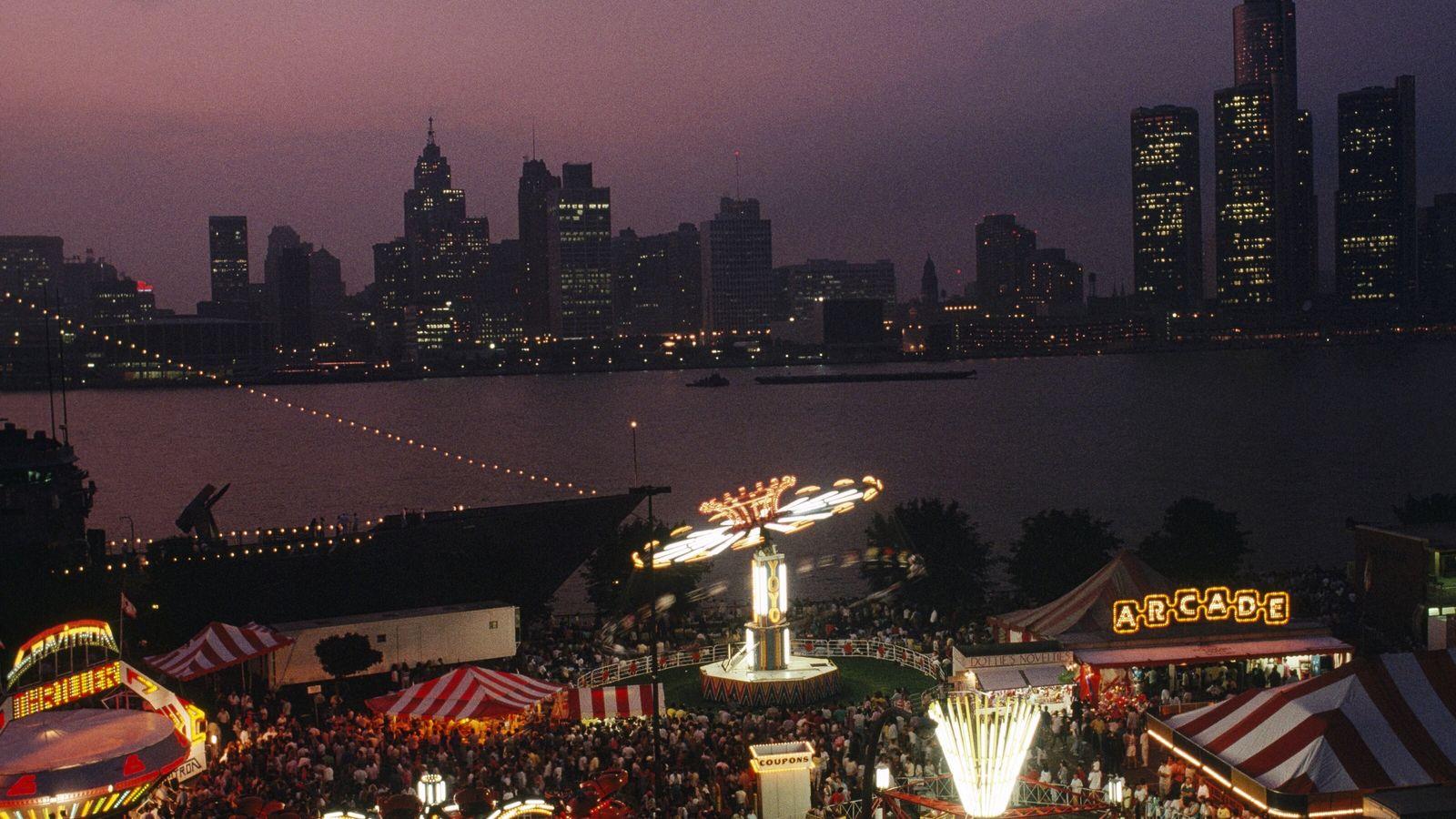 Imagen de una feria en Ontario por la noche con el skyline de Detroit en el ...