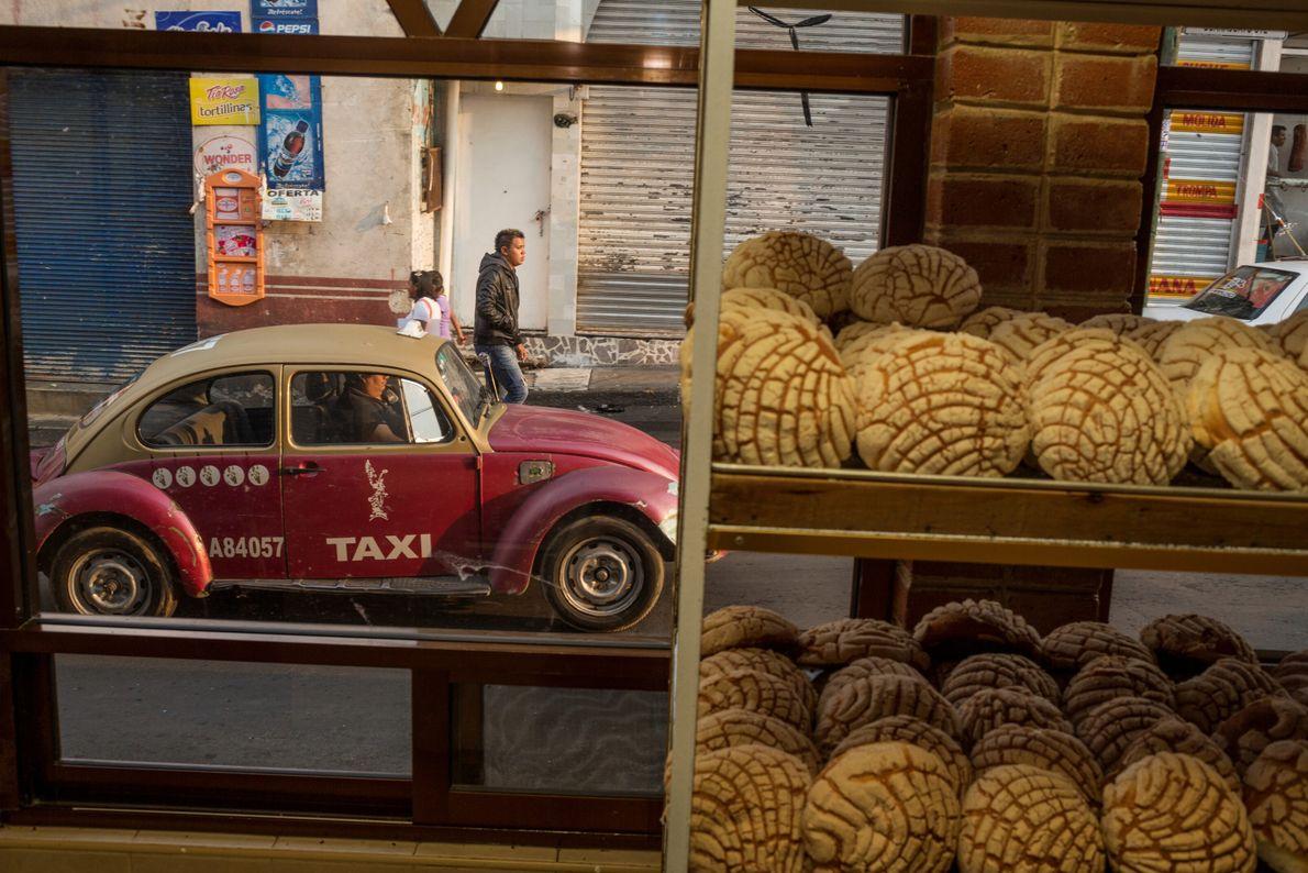 Imagen de unas hogazas de pan en el escaparate de una panadería, con un taxi rojo ...