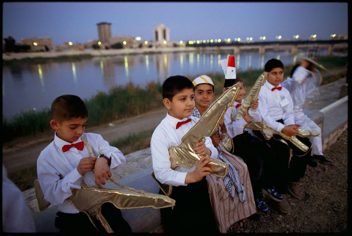 Imagen de escolares iraquíes con camisas blancas y pajaritas rojas, llevando metralletas doradas falsas.