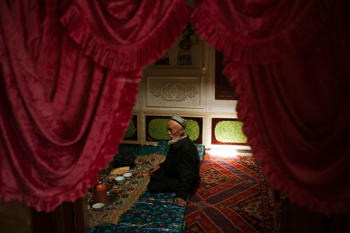 Imagen de un hombre mayor sentado entre alfombras en Kashgar, Xinjiang China, preparándose para tomarse su ...