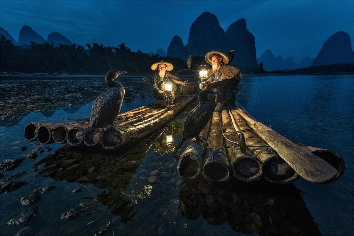En una tarde de otoño en Guilin, China, dos pescadores y sus cormoranes entrenados descansan en ...