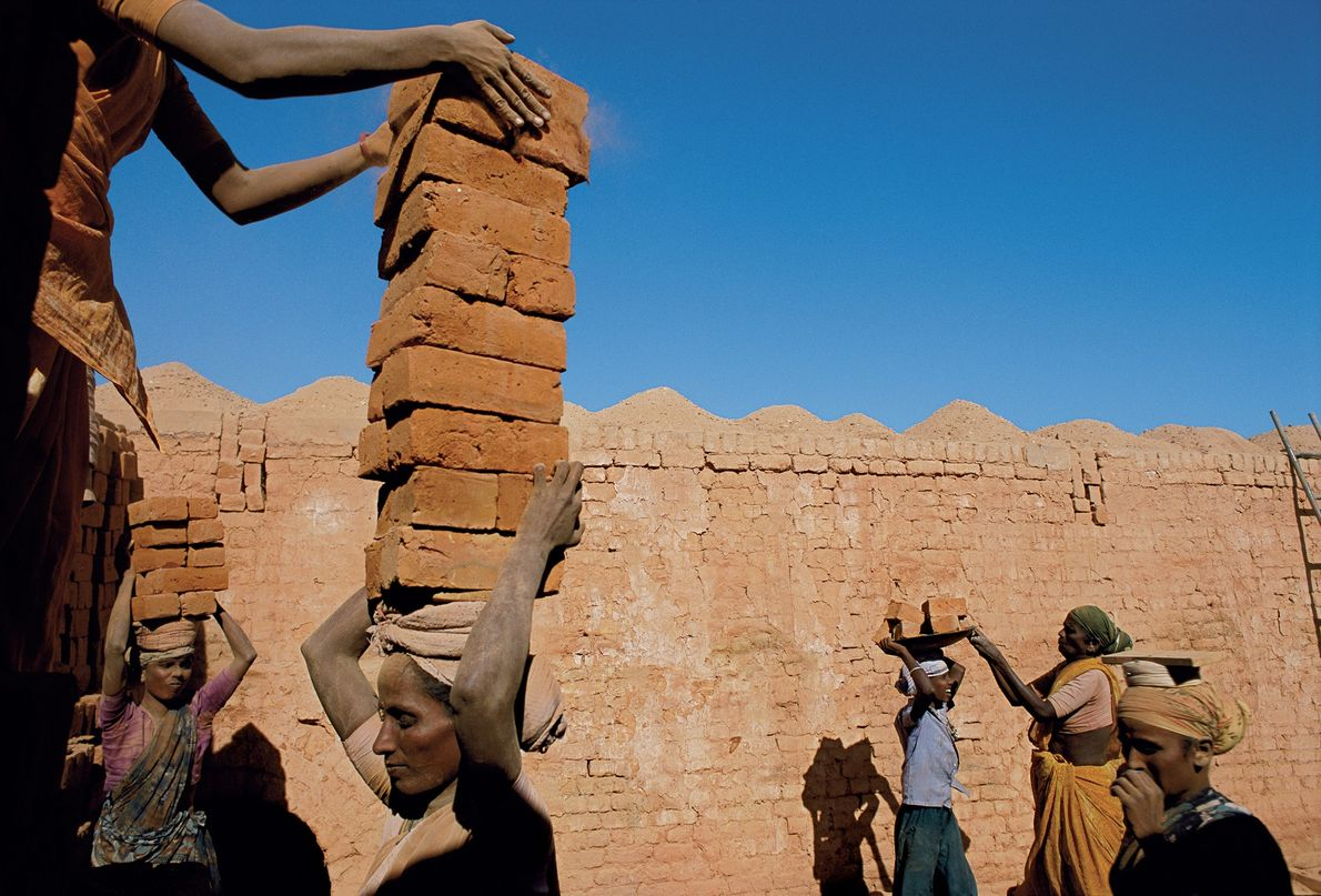 2002 , INDIAEn India, una familia de jornaleros endeudados apila y transporta ladrillos para pagar sus …