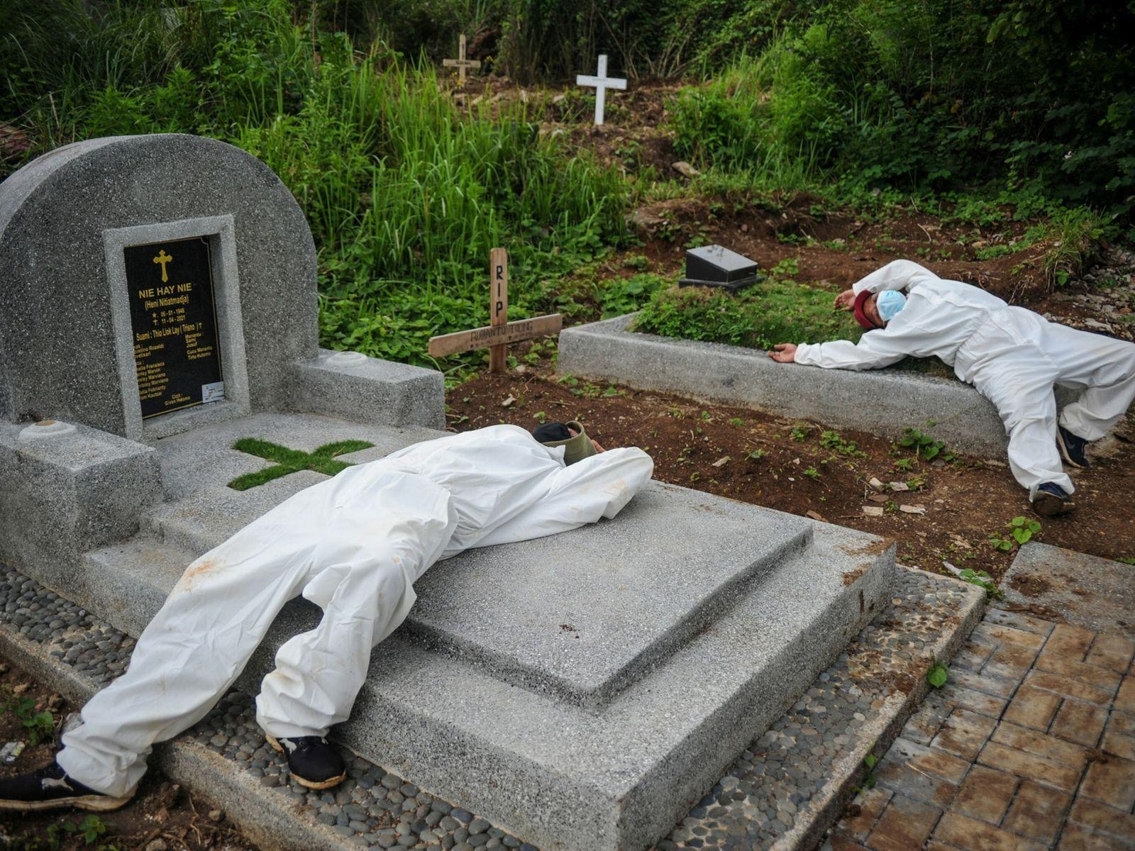 Trabajadores descansan tras enterrar a una víctima de la COVID-19