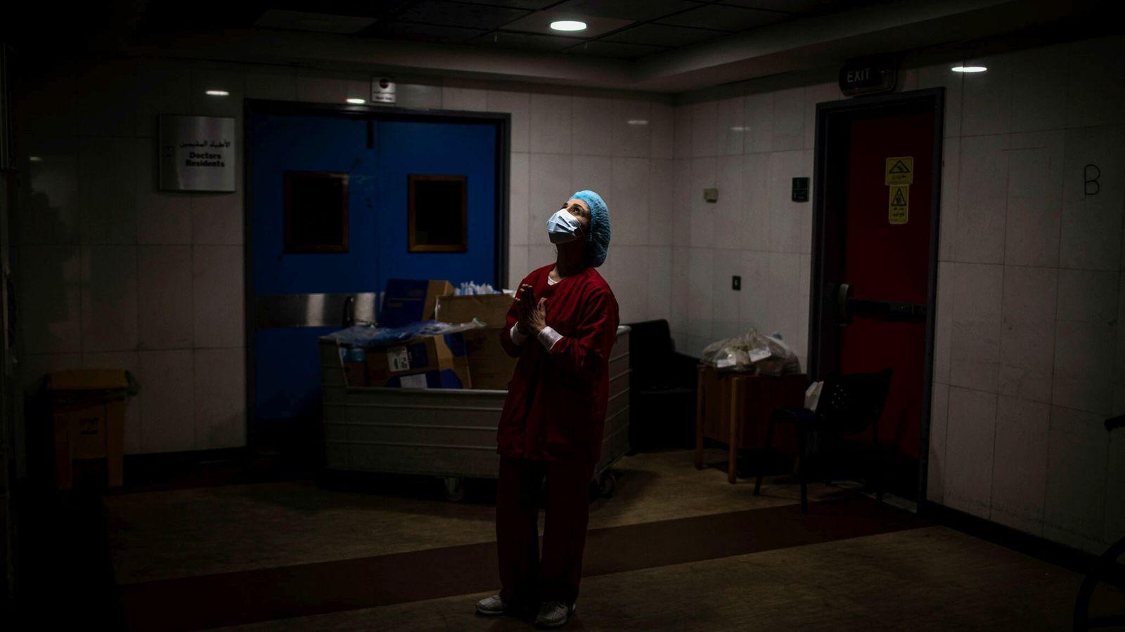 Fotografía de una enfermera rezando en la UCI